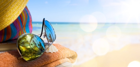 Straw hat, bag and sun glasses  on a tropical beach